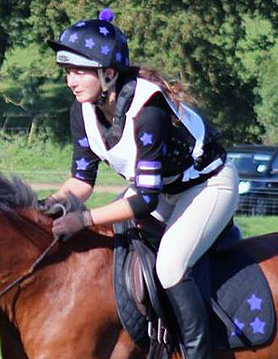 Charlotte in purple and black xc gear going over jumps