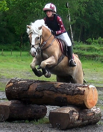 Izzy jumping in burgundy cross country baselayer and matching hat cover