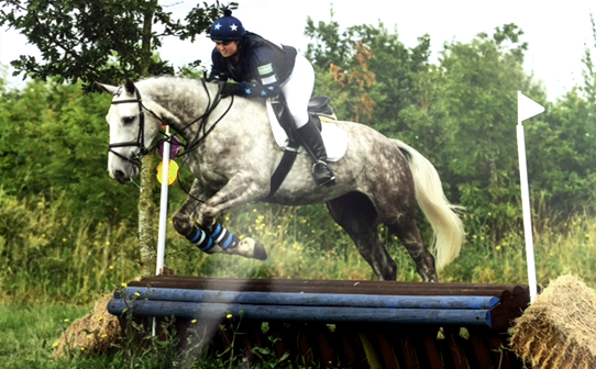 Navy blue XC colours jumping with sky and white stars