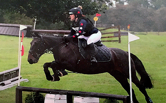 Natalie and Rosie going over XC jump in rainy contions
