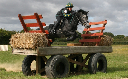 Oliver jumping hay cart in bottle green polo and hat with yellow xc diamonds