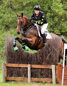 Black and green ladies xc colours going over brush jump