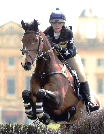 XC colours and custom hat silk jumping at Badminton in front of Badminton House